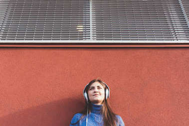 portrait young woman outdoor in the city listening music headphones