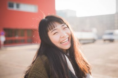 portrait young beautiful asian woman outdoor back light looking camera smiling