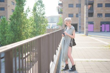 young woman listening music using smartphone in the city