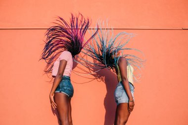 two women sisters dancing moving hair outdoor
