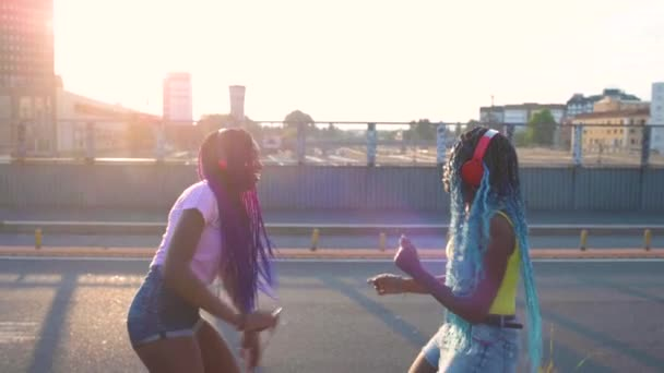 Slow motion of two young black sisters dancing outdoor at sunset  freedom, cheerful, carefree concept