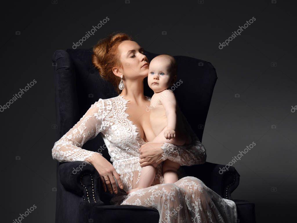 Junge Mutter Frau sitzen und halten ihr schönes Kind Kind