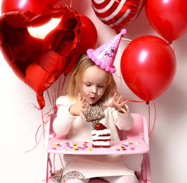 Little baby girl kid celebrate birthday with sweet cake and candies