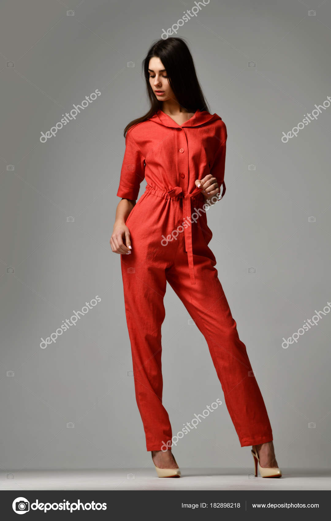 31678e978718 Νεαρή όμορφη γυναίκα που παρουσιάζουν στο νέο casual Μόδα κόκκινο κοστούμι  φόρεμα με παντελόνι και γεμάτο σώμα κουκούλα σε γκρι φόντο — Εικόνα από ...
