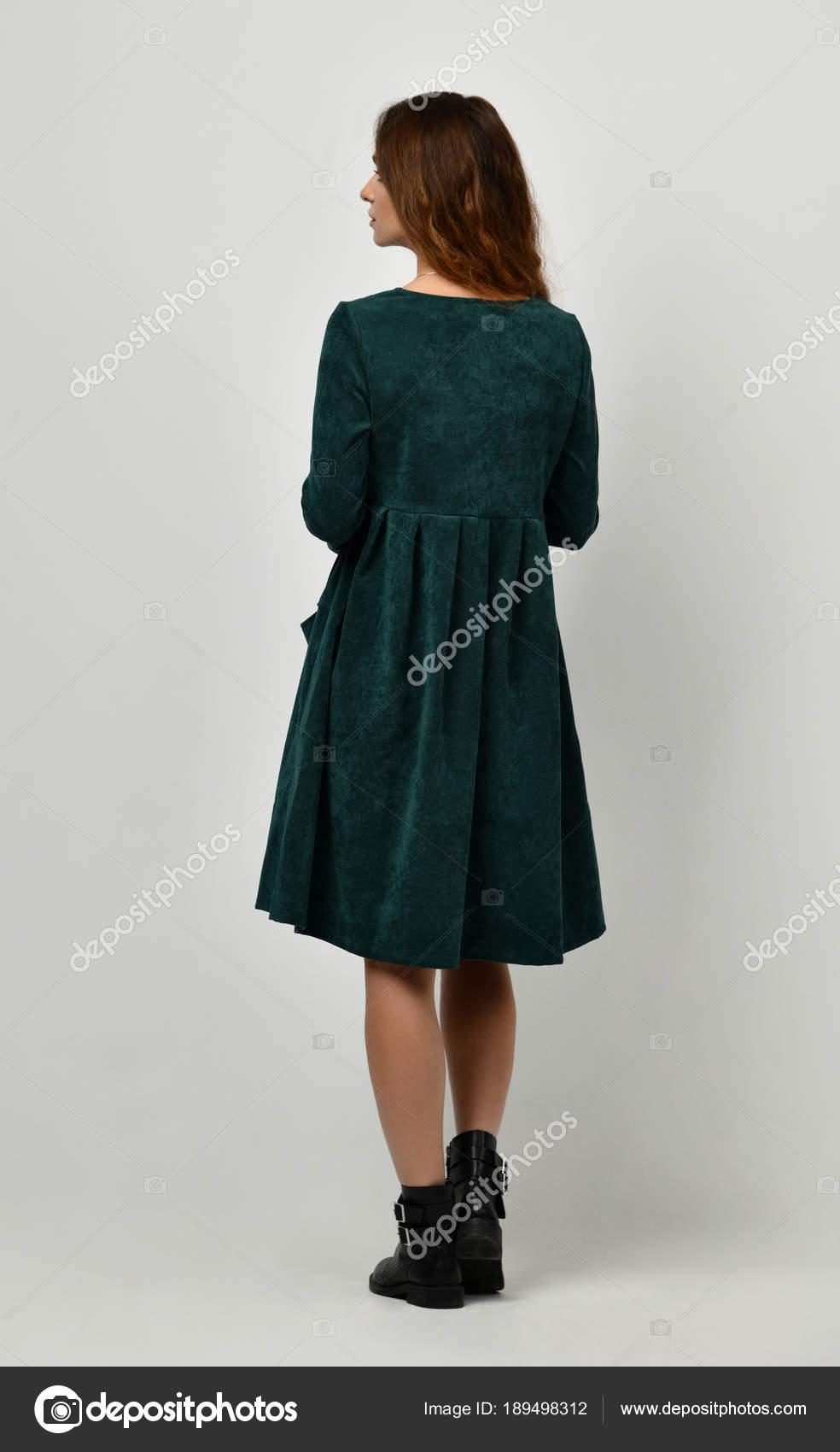 a3b29657607e23 Jonge mooie vrouw poseren in nieuwe casual winter groene jurk op grijs —  Stockfoto