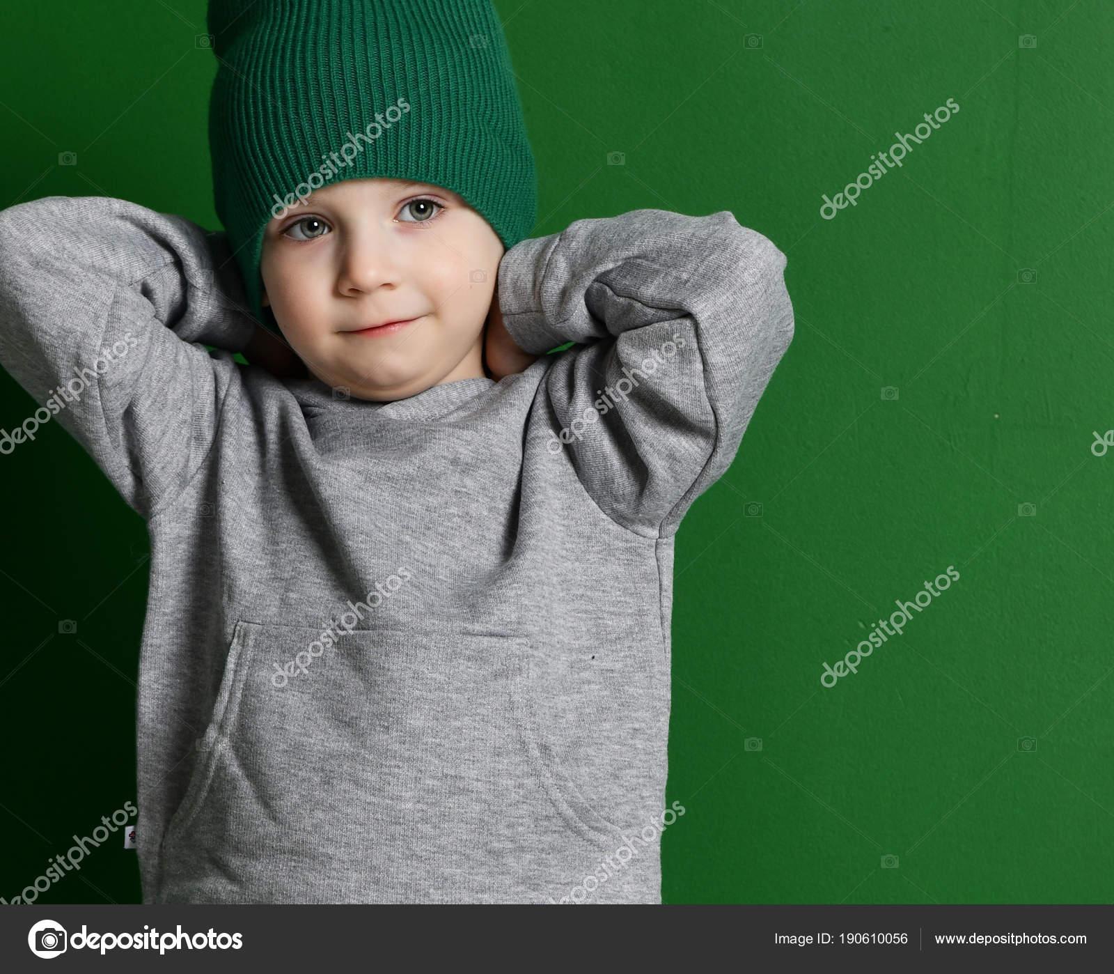 Pré-escolar menino crianca no suéter cinza com capuz e chapéu de inverno em  fundo verde hortelã — Fotografia por dml5050 69a234fe596