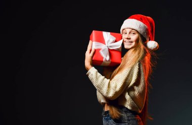 Happy smiling teenager girl with braces in red cap with pompon is holding her christmas gift red box with ribbon