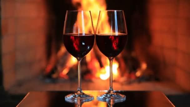 Dvě sklenice červeného vína u krbu