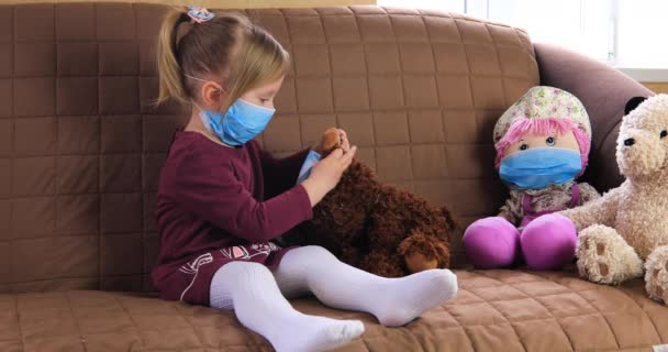 Girl in a medical mask playing doctor with her toys.