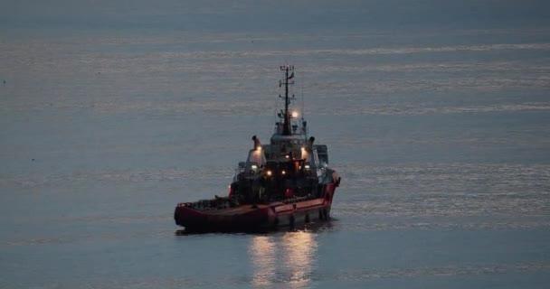 Loď na moři po západu slunce. Loď, pozadí pohledu na loď. Průmyslová doprava na večerním pobřeží. Obchodní odvětví obchodních plavidel. Rybí loď, loď. Rybářská loď plující po vodě. Klidný večer