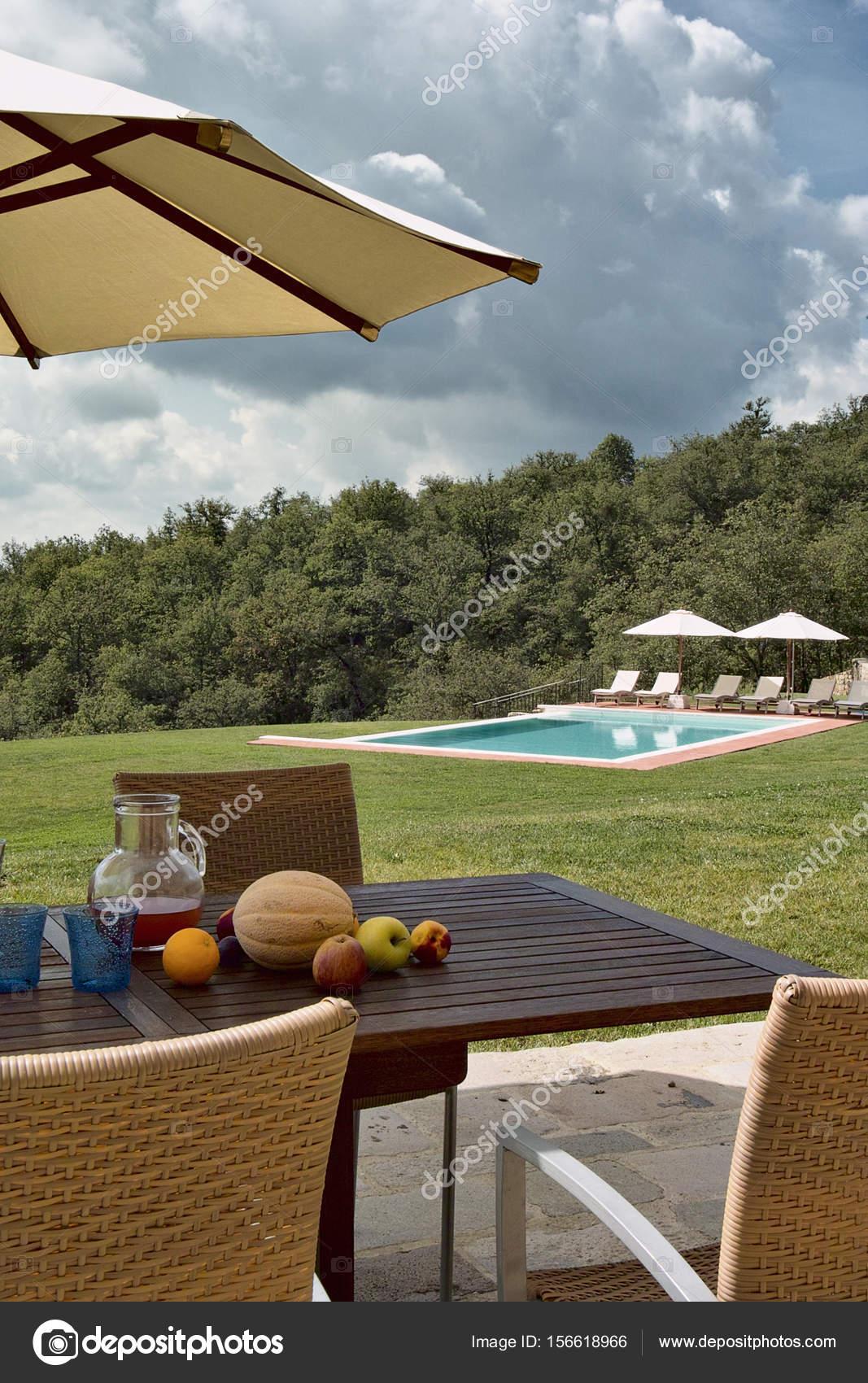 fruits on the table under the beach umbrella and swimming-pool ...