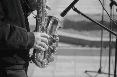 man plays the saxophone on the street monochrome