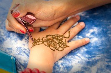 professional drawing mehendi on female hand