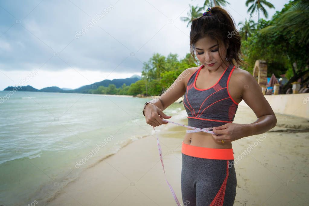 Young girl in sportswear with tape-measure at sea beach.fit Caucasian female measuring waist on beach - weight loss, summer diet concept.Beautiful sporty woman body with tape measure.