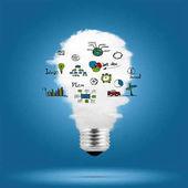 Žárovka s cloud uvnitř a obchodní náčrtky nad modrým pozadím