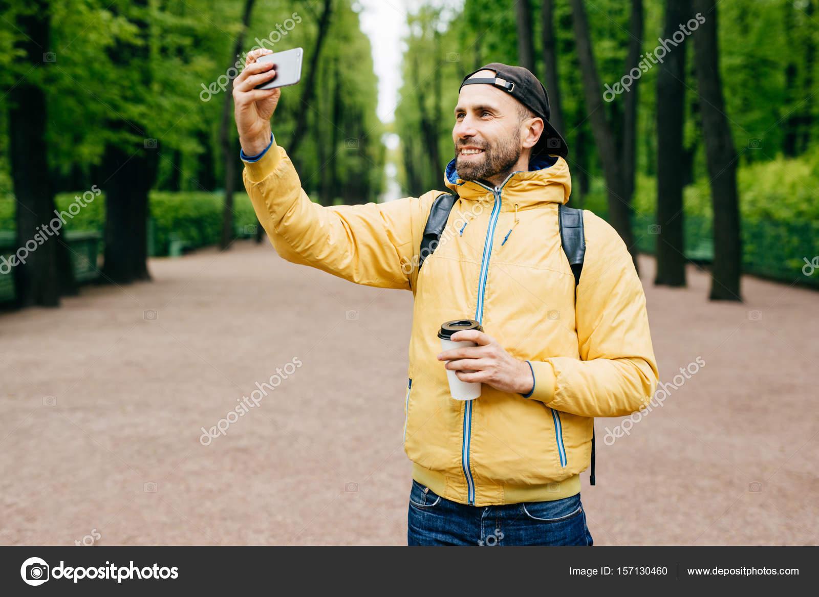 71830e8940 Na białym tle portret hipster facet sobie modne ubrania odpoczynku w parku  sam podziwiając pogodny i świeżego powietrza. Brodaty mężczyzna co selfie w  parku ...