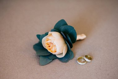 Artificial beige rose and wedding rings lying on white soft background. Bride`s details. Composition of bride`s accessories. Gold rings of happy couple going to marry