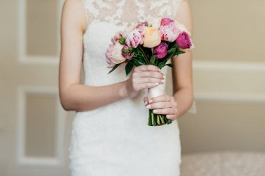 Wedding bouquet in bride's hands. Slim bride in white dress holding beautiful flowers in hands, going to marry, waiting for her future husband. Bridal bouquet. Wedding concept