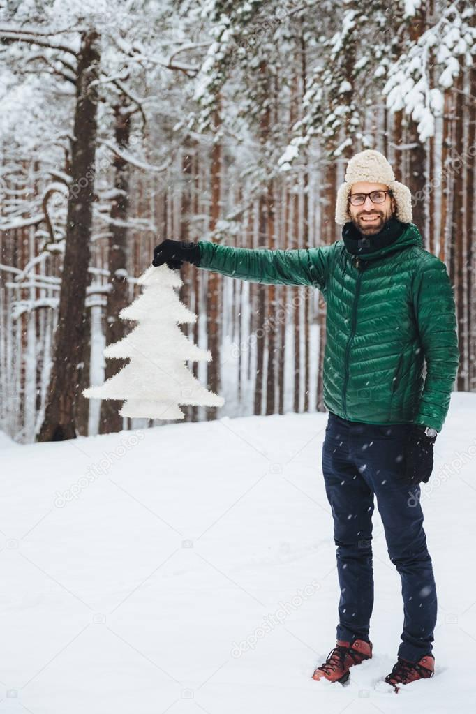 Vertical portrait of positive smiling male wears fashionable warm clothes, keeps white fir tree in hands, poses in white winter forest. Happy unshaven attractive man spend free time or winter holidays