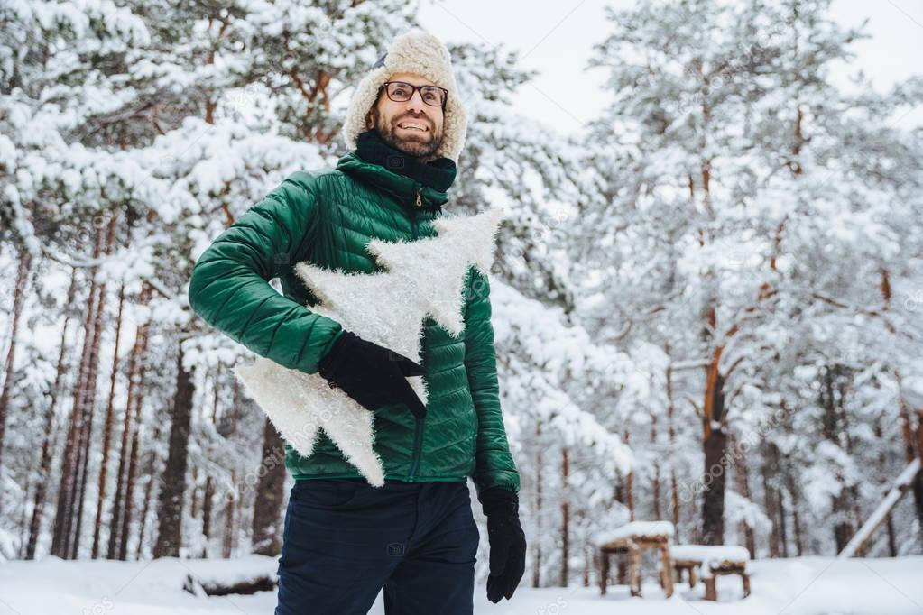 Cheerful male model dressed in winter clothes, holds white artificial fir tree, stands in winter forest, has pleasant smile, enjoys beautiful landscapes. People, holidays, recreation concept