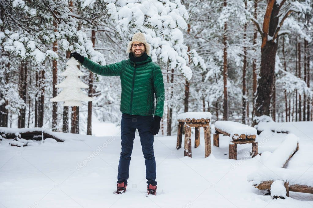 Full growth portrait of cheerful smiling male demonstrates white artificial fir tree, stands in winter forest has happy expression, glad to spend time outdoors. Winter and season concept