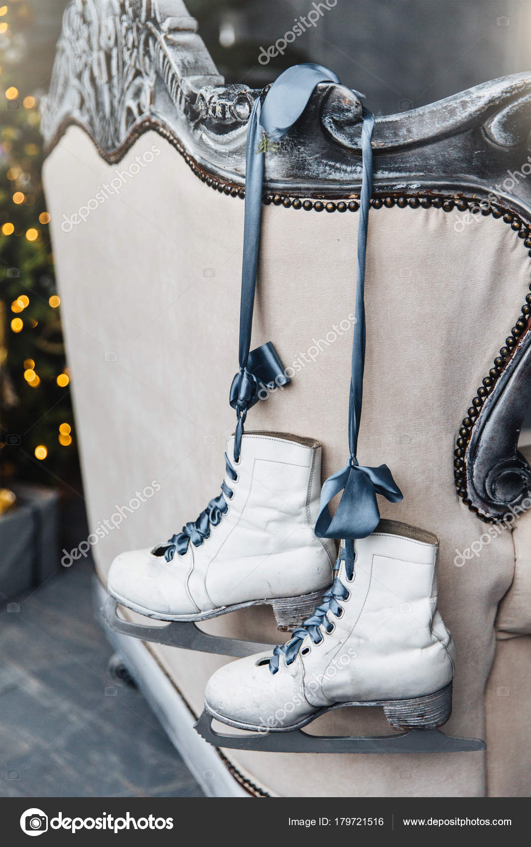 Pair of ice skates hang on ribbon on ancient sofa, wait for their ...