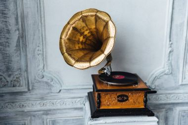 Old gramophone with horn speaker stands against anicent background, produces songs recorded on plate. Music and nostalgia concept. Gramophone with phonograph record