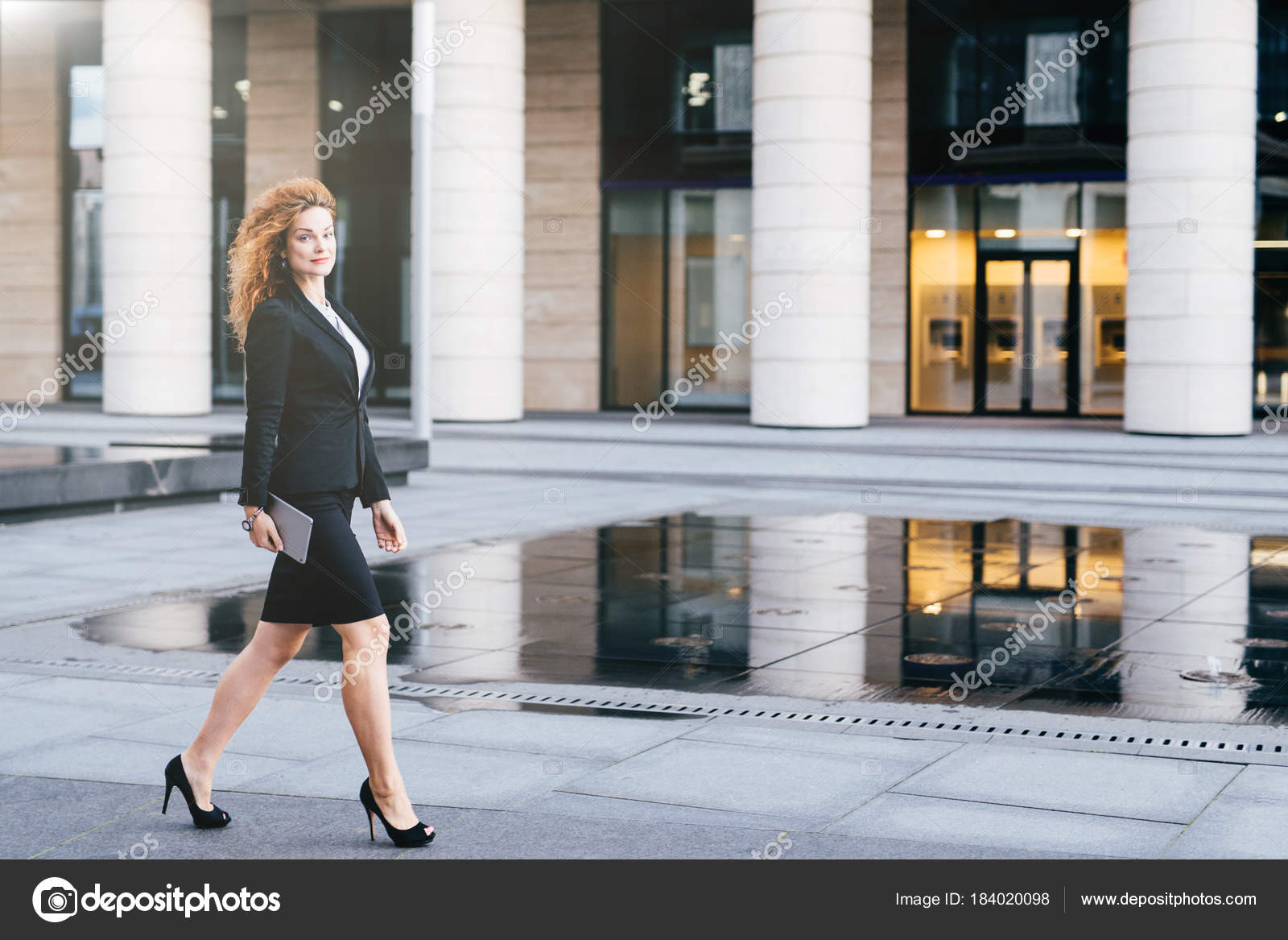 dde4e73a1362f Elegant slim woman in black suit and high-heeled shoes, holding tablet in  hands going for work. Businesswoman ...