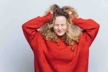 Stressful frustrated blonde woman tears out hair, regrets wrong doing, expresses negative emotions, wears loose red sweater, isolated over white studio background. Emotional young female indoor