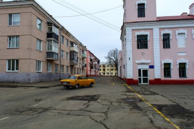 Old yellow car Moskvich on the road in the city center Polotsk, Belarus, Vitebsk region, March, spring day,
