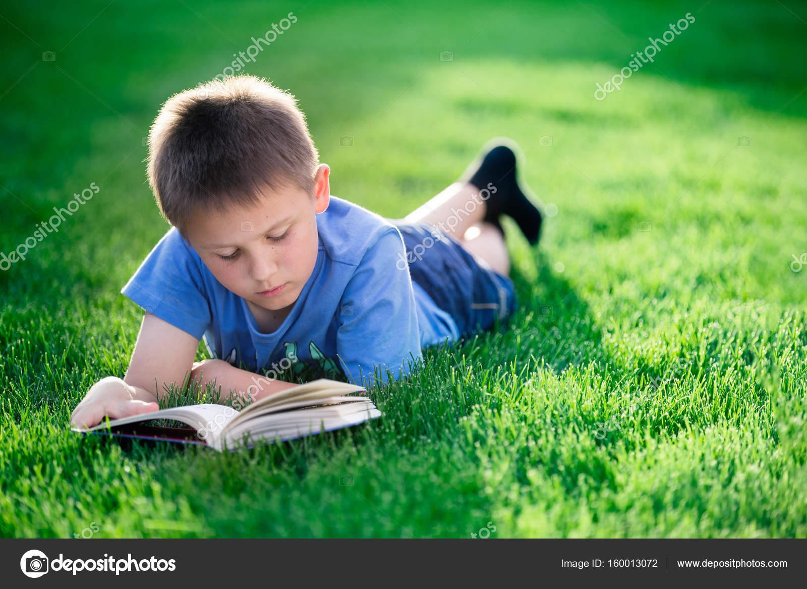 Junge Buch zu lesen, liegend auf dem grünen Rasen — Stockfoto ...