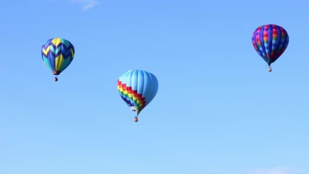 Vícebarevné horkovzdušné balónky létající nad modrou oblohou
