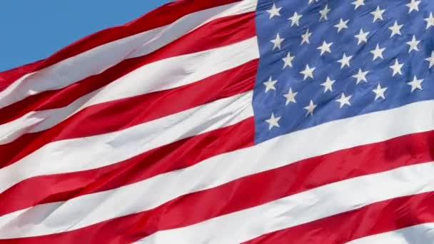 American flag waving in the wind on blue sky, US flag slow motion close-up, United States of America national flag, 4k