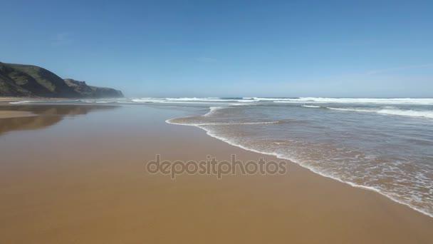 Atlantský oceán bouří na písečné pláži.