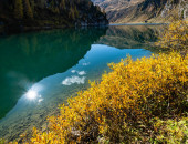 Sunny autumn alpine Tappenkarsee lake and rocky mountains above,