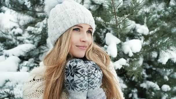 Blond žena v zimní krajině poblíž jedle