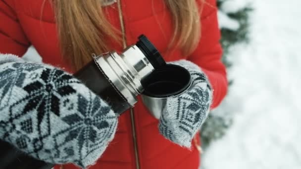 Young woman warm with tea from thermos on frost outdoor.
