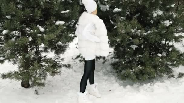 High model posing in a white dress in a green tree in the winter.