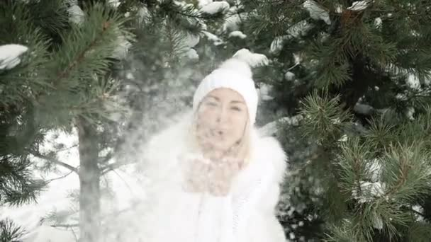Young beautiful smiling blonde blast snow with her hands.