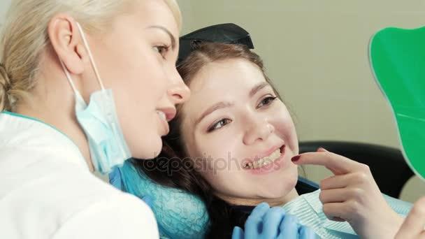 Healthy white woman teeth and dentist mouth mirror closeup