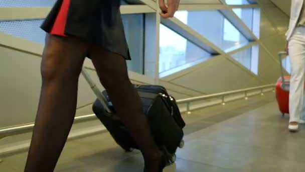 Two women walk down hallway at airport terminal waiting room