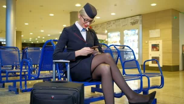 Na letišti se nachází letuška se zavazadly a držení smartphone