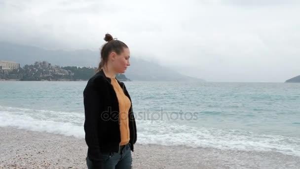 V zatažené mlhavé ráno žena chůze na pláž s vlnami