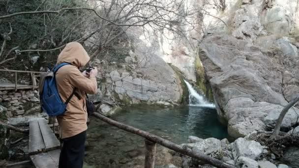 Mann steht auf hölzerne Brücke über den Fluss im Wald, fotografieren