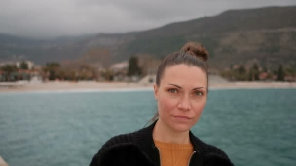 close shot of woman face on shore of lake, looking into camera
