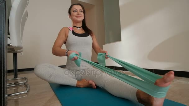 Sporty woman doing exercises with tight band fitness at home indoors