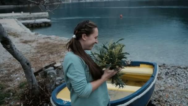 Dospělý Kavkazský žena je šťastná obdržet kytici Mimosa nedaleko jezera