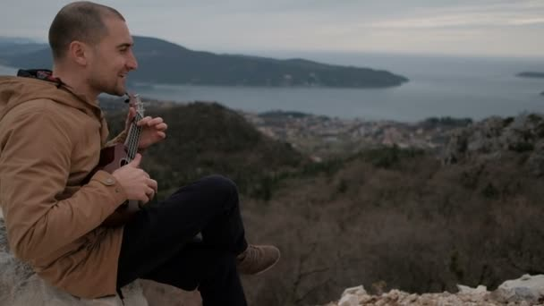 Young man sits on hill, sings and plays Hawaiian ukulele outdoors.