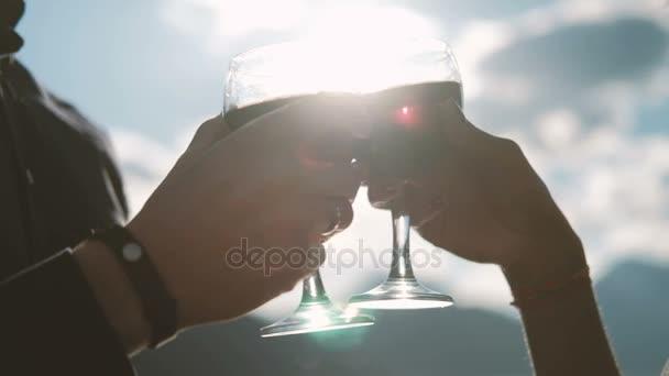 Mann und Frau trinken Wein in Gläsern gegen den blauen Himmel.