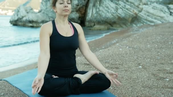 An adult woman sits in a lotus position on the beach near stone rocks.